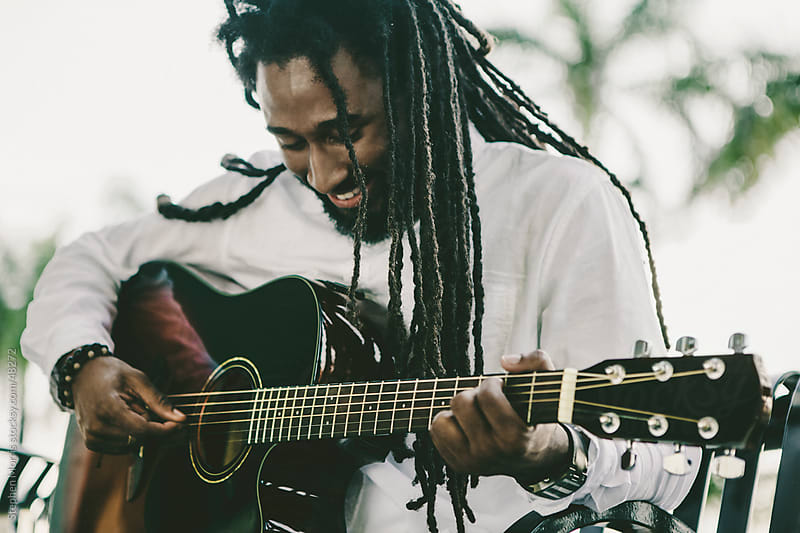 Young Man with Dreadlocks Playing Guitar by Stephen Morris for Stocksy United
