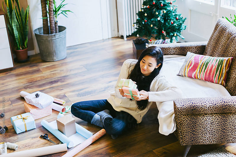 Happy asian woman holding Christmas gifts. by BONNINSTUDIO for Stocksy United