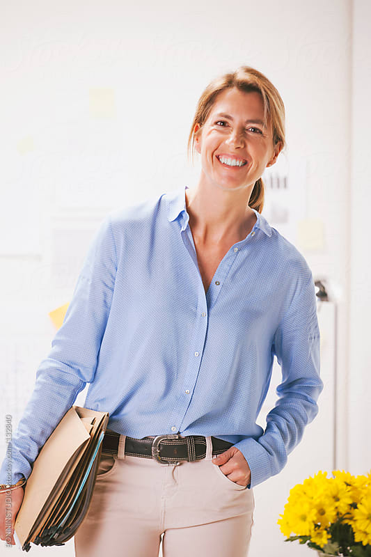 Beautiful mature business woman standing with documents at home office. by BONNINSTUDIO for Stocksy United