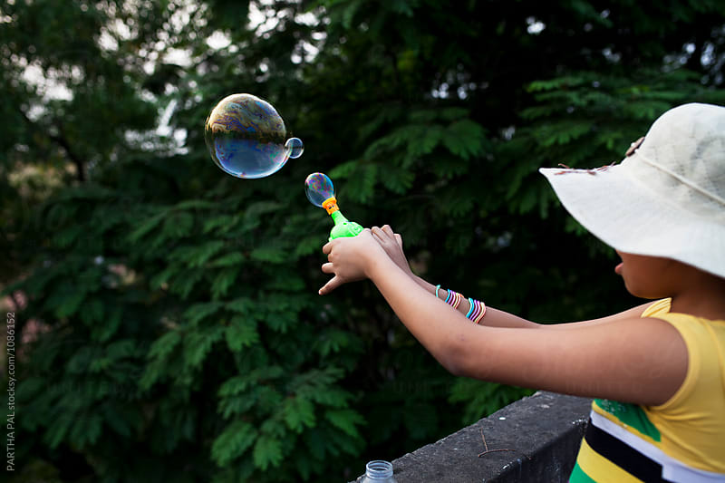 Teenage girl playing and making fun with bubble by PARTHA PAL for Stocksy United