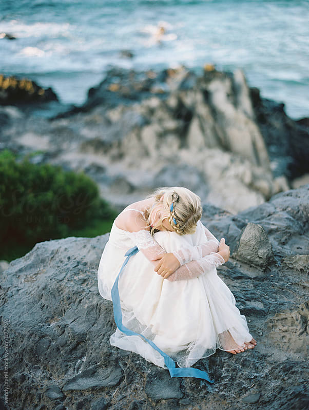 bride curled up on rocks overlooking ocean by wendy laurel for Stocksy United
