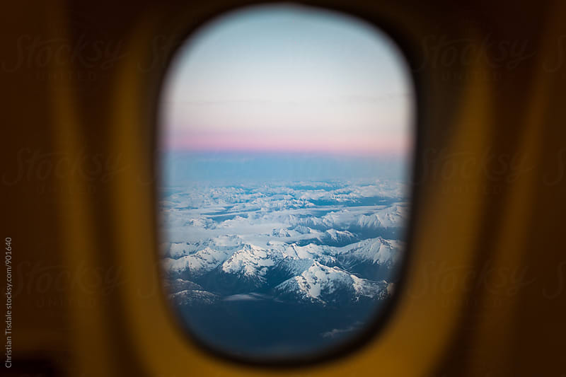 View of mountains at sunrise from airplane window by Christian Tisdale for Stocksy United