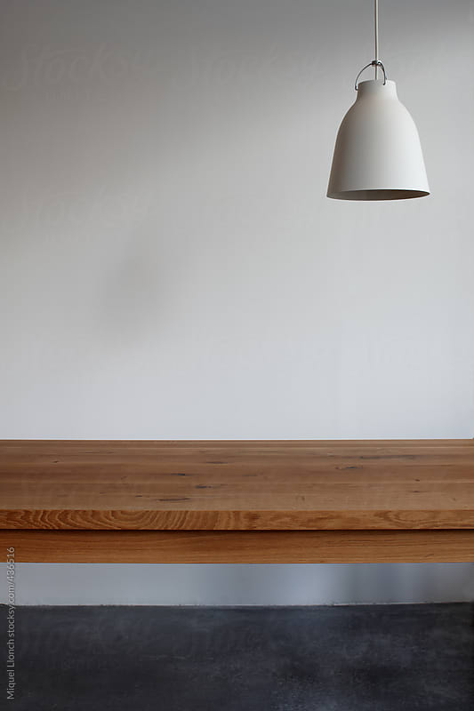 Interior design with wooden table and hanging lamp by Miquel Llonch for Stocksy United