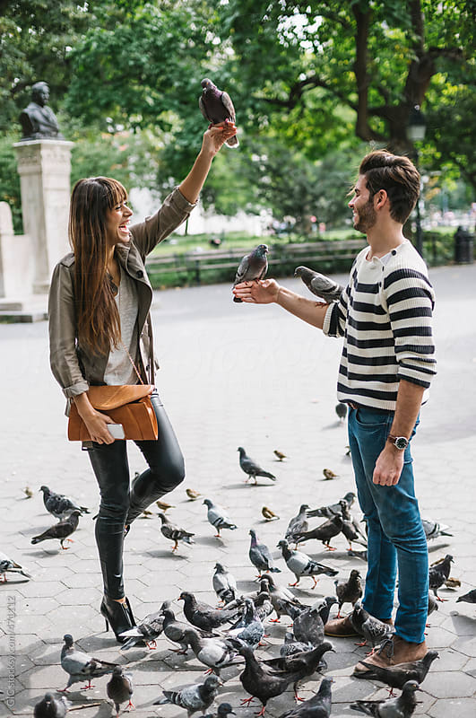 Young couple having fun with pigeons in New York City by GIC for Stocksy United