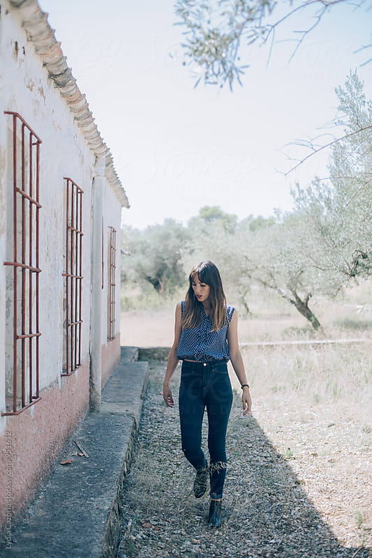 Girl walking near an old home by Lydia Cazorla for Stocksy United