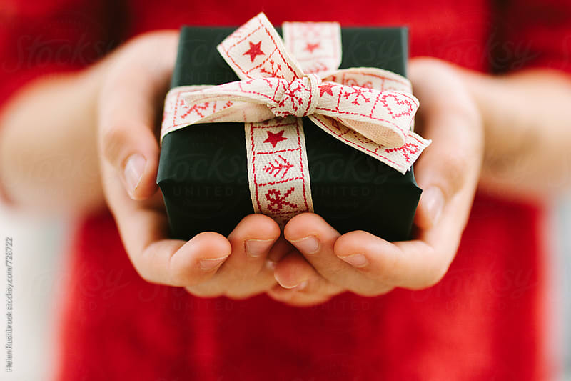 Hands holding a red, white and black Christmas gift. by Helen Rushbrook for Stocksy United