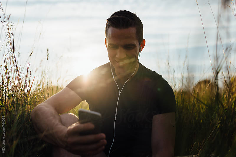 Runner Listening Music Playlist on the Mobile Phone by HEX. for Stocksy United