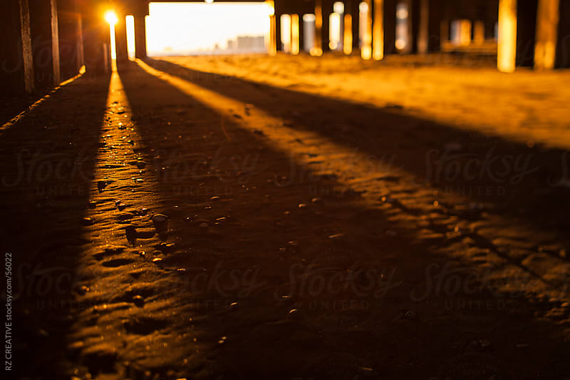 Selective focus (tilt-shift) picture of the sun setting through a pier. by Robert Zaleski for Stocksy United