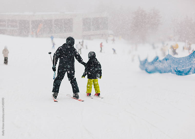 father teaches his child to ski by Kelly Knox for Stocksy United