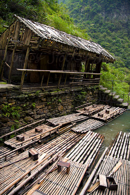 Shelter on the embankment and many rafts made of bamboo by Alice Nerr for Stocksy United