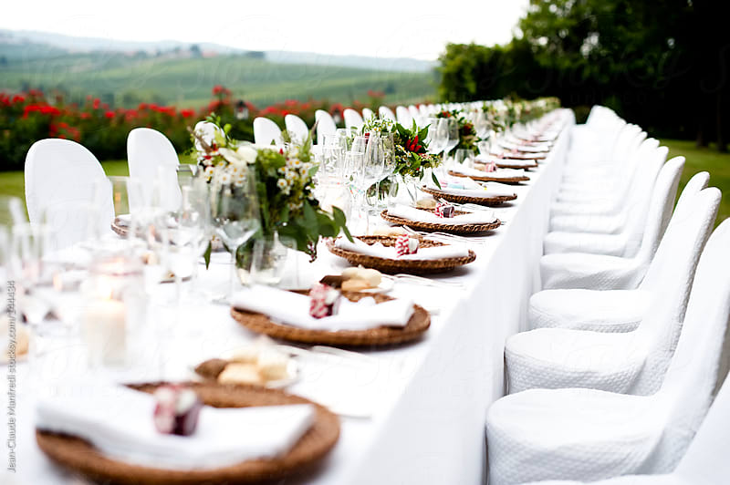 Table at a wedding reception in an outdoor reception, immersed in the Tuscan hills. by Jean-Claude Manfredi for Stocksy United