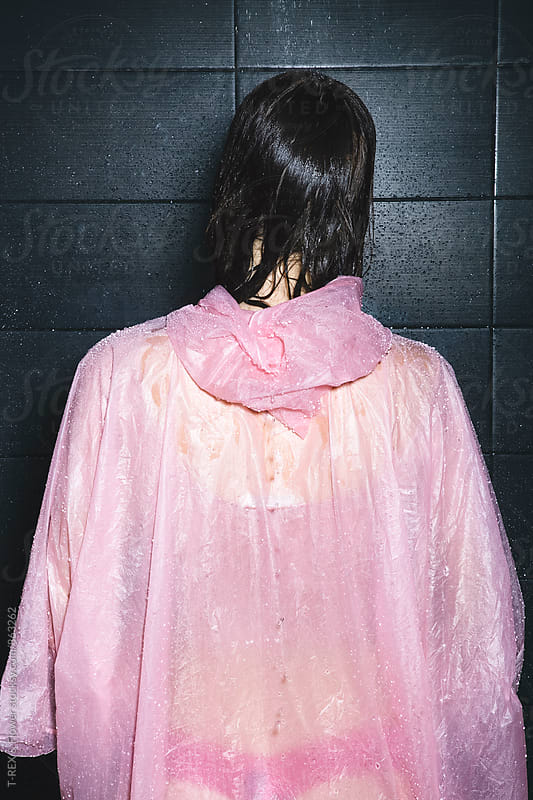Back view of woman in pink raincoat taking a shower by Danil Nevsky for Stocksy United