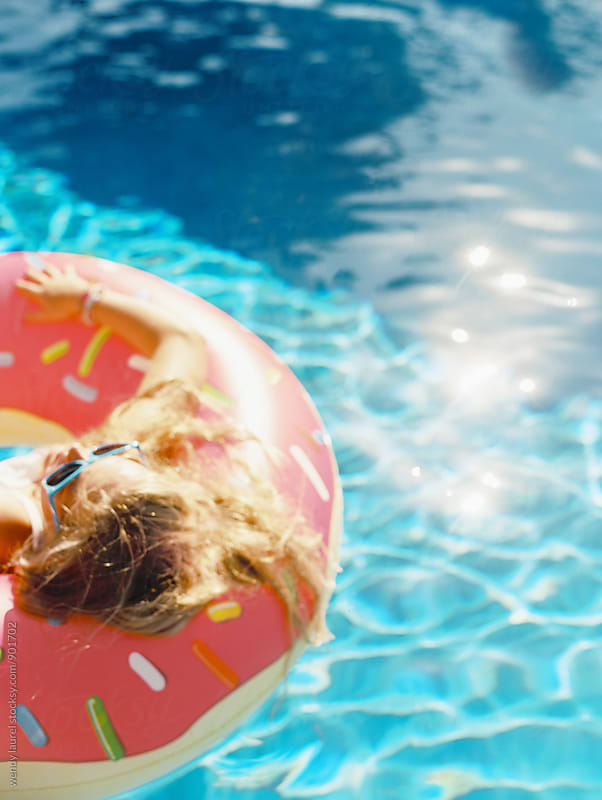 blonde girl in sunglasses floating in swimming pool in pink donut floatie by wendy laurel for Stocksy United