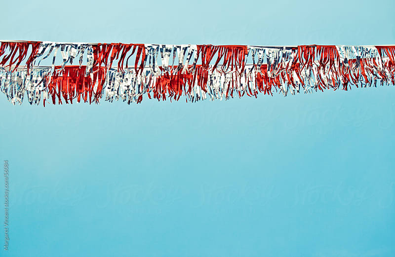 red and silver streamers wave in the air by Margaret Vincent for Stocksy United