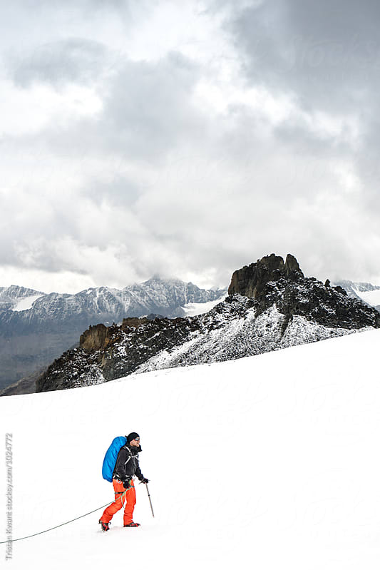 Male hiking on a glacier by Tristan Kwant for Stocksy United