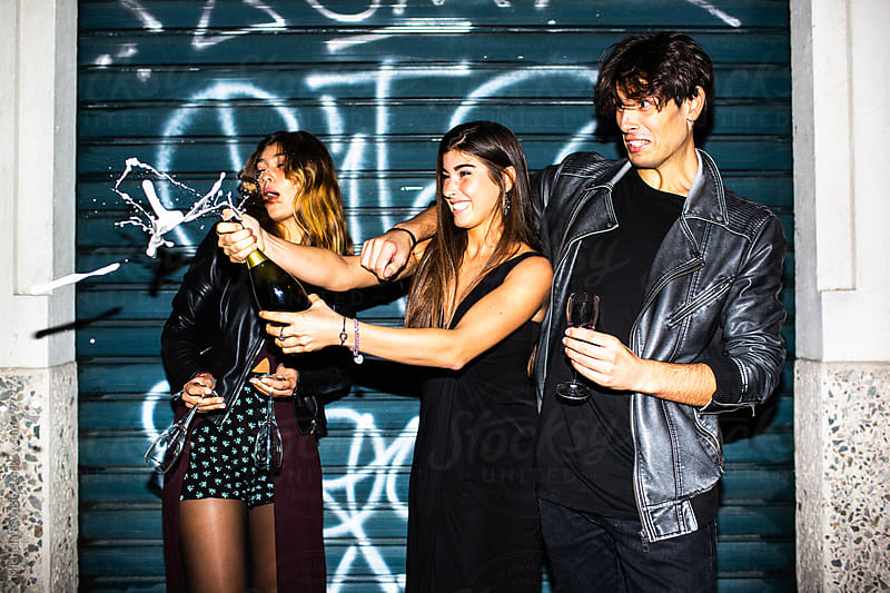 Friends celebrating with champagne outdoors by michela ravasio for Stocksy United