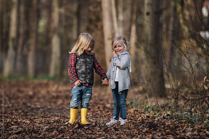 little boy and girl - the first love - holding hands in an autumnal forest by Leander Nardin for Stocksy United