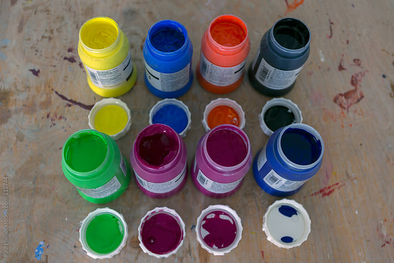 Pots of vibrant acrylic paint for use in a school art class by Paul Phillips for Stocksy United