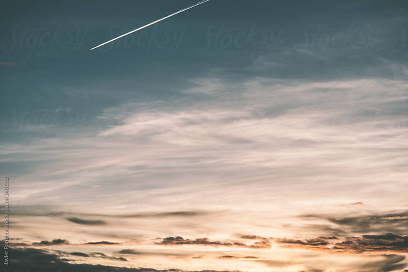 Plane on route at sunset by Javier Pardina for Stocksy United