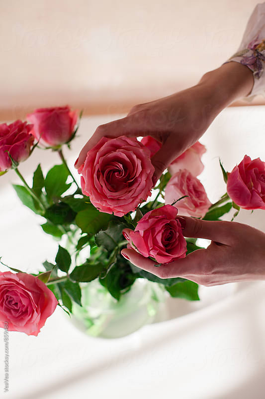 Woman arranging bouquet of roses indoor by VeaVea for Stocksy United