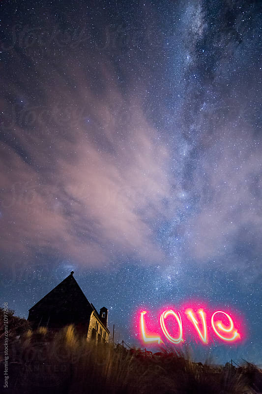 A woman writing the word 'love' with red light under the Galaxy, by Song Heming for Stocksy United