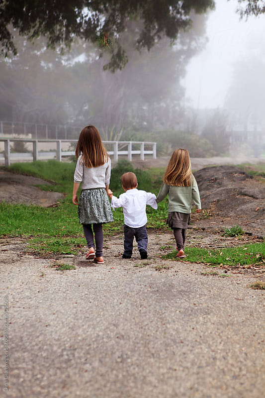 Three Children Walking Away in Foggy Outdoors by Dina Giangregorio for Stocksy United