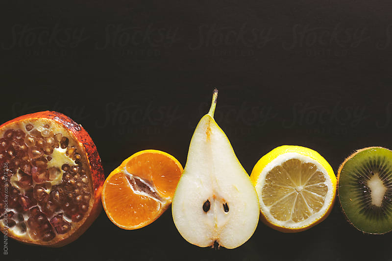 Overhead of sliced variety of fruits on black background. by BONNINSTUDIO for Stocksy United