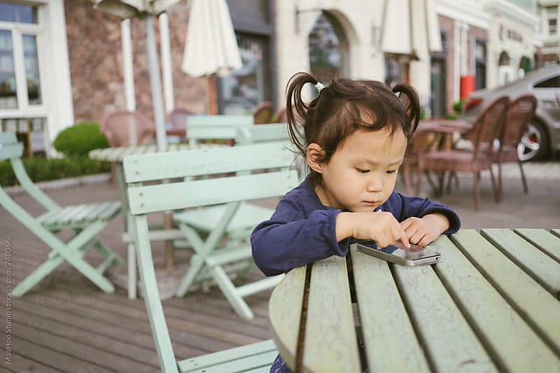 Toddler girl using smart phone in a outdoor restaurant by Maa Hoo for Stocksy United