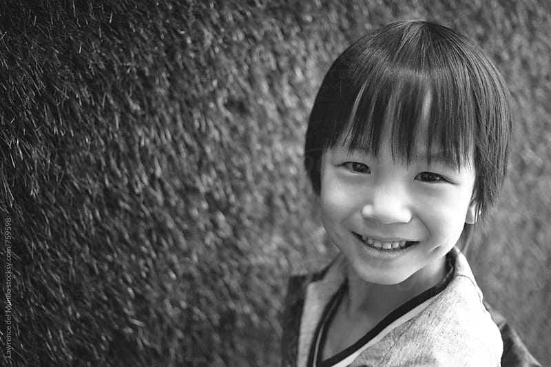 Black and white portrait of a cute, adorable, young kid looking at camera by Lawrence del Mundo for Stocksy United