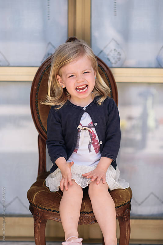 Cute little girl making funny faces  by Adrian Cotiga for Stocksy United
