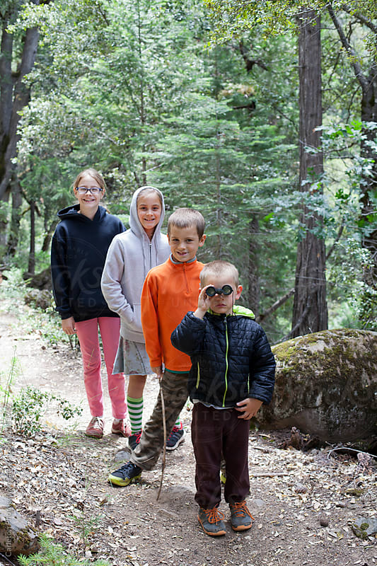 Four kids out for a hike on a trail by Carleton Photography for Stocksy United