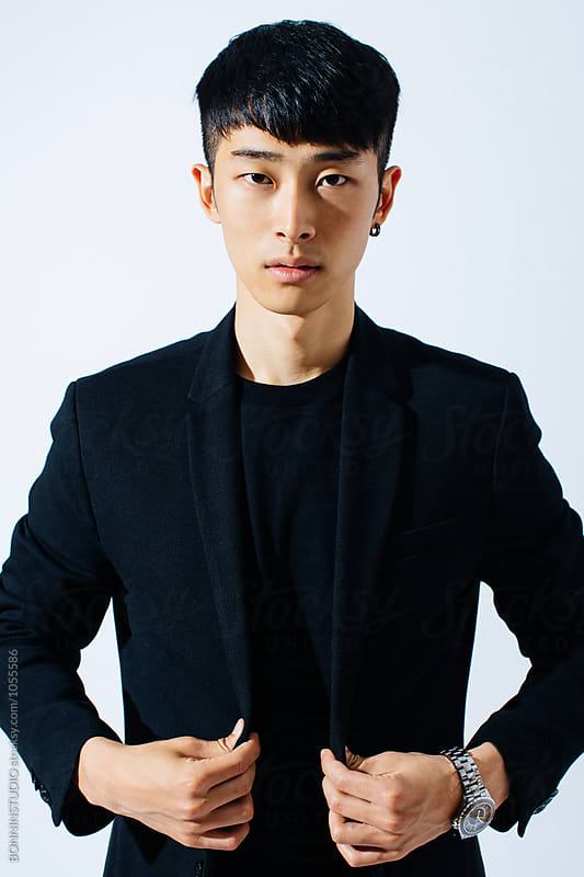 Portrait of an attractive asian man wearing a black suit.  by BONNINSTUDIO for Stocksy United