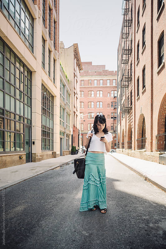 Casual Woman Using Cellphone in a Tribeca Street in New York by Joselito Briones for Stocksy United