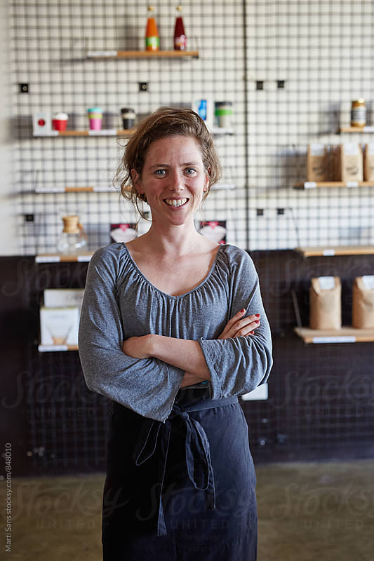 Portrait of smiling woman wearing apron and looking at camera by Martí Sans for Stocksy United
