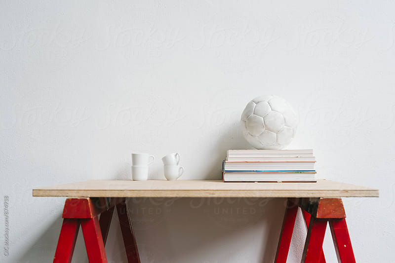 Table with books, ball and coffee cups by Simone Becchetti for Stocksy United