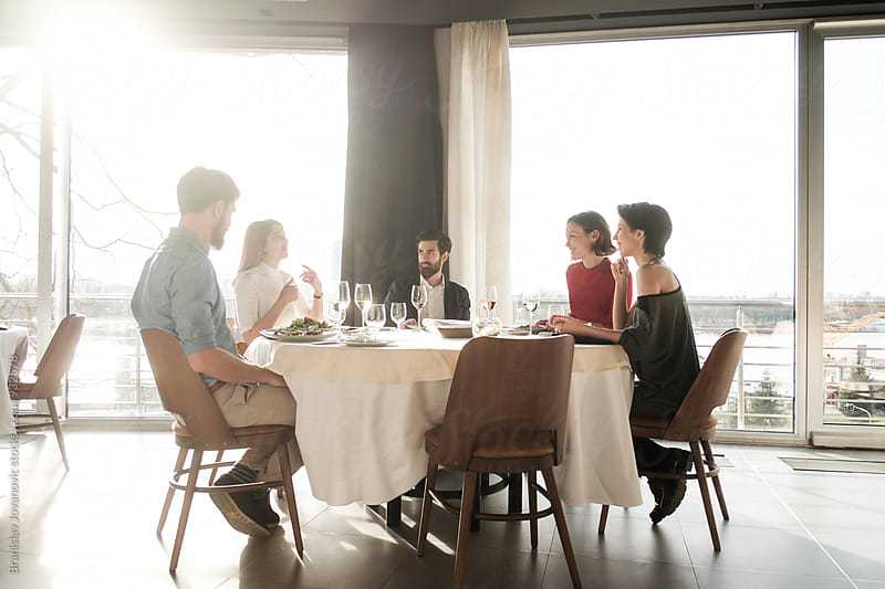 Group of  Freinds Having Lunch at the Restaurant by Branislav Jovanović for Stocksy United