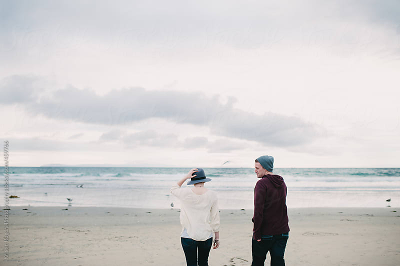 Couple on a date walking on cloudy beach day by Kristin Rogers Photography for Stocksy United