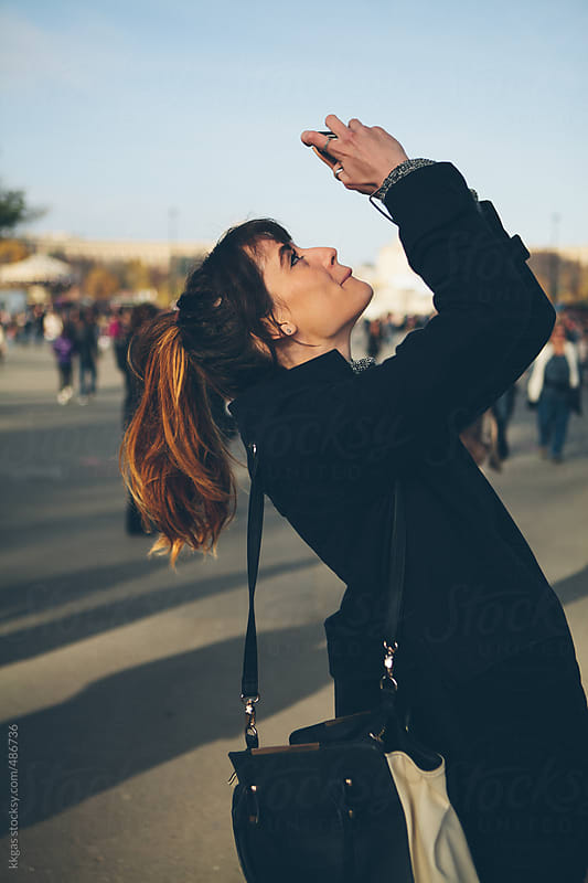 Attractive young woman taking a photo using her smartphone by kkgas for Stocksy United
