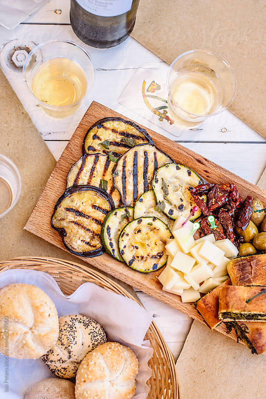 Food: italian antipasti, grilled vegetables, cheese, dried tomato with bread and white wine by Ina Peters for Stocksy United