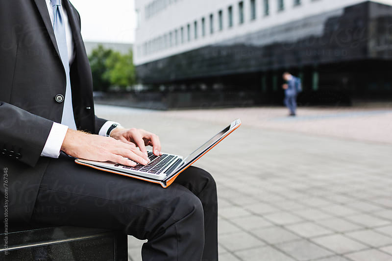 Man in suit using laptop outdoors by michela ravasio for Stocksy United