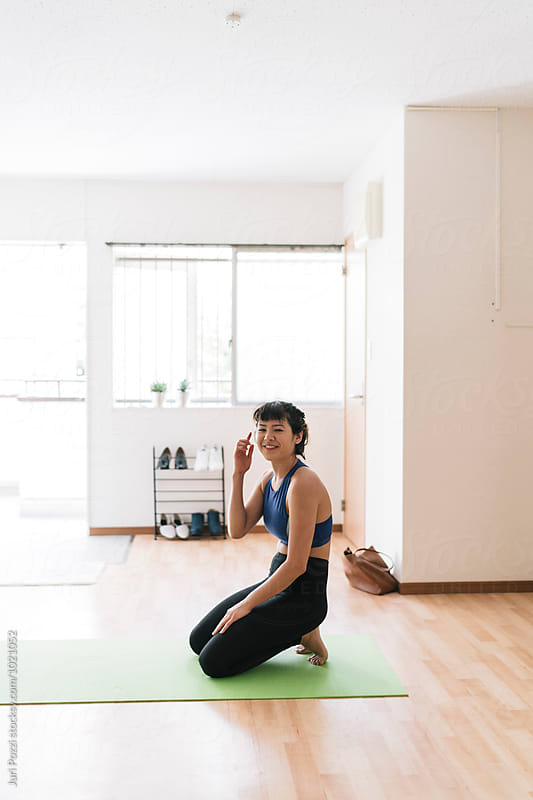 Young Asian woman doing yoga in her apartment in Japan by Juri Pozzi for Stocksy United