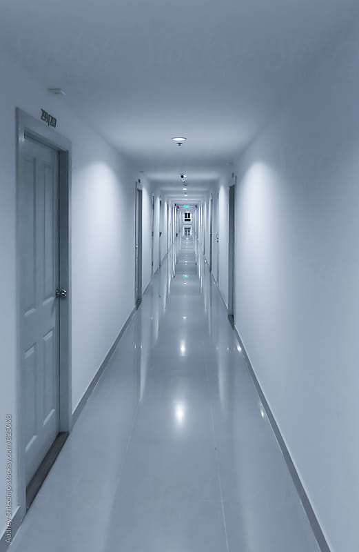 White corridor in perspective with doors on both sides. by Audrey Shtecinjo for Stocksy United