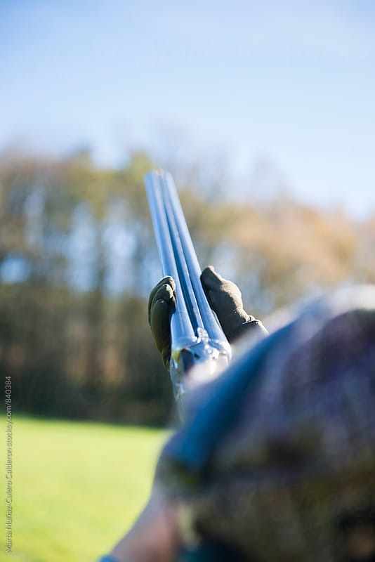 Woman holding a shotgun in a hunt ducks and pheasants by Marta Muñoz-Calero Calderon for Stocksy United
