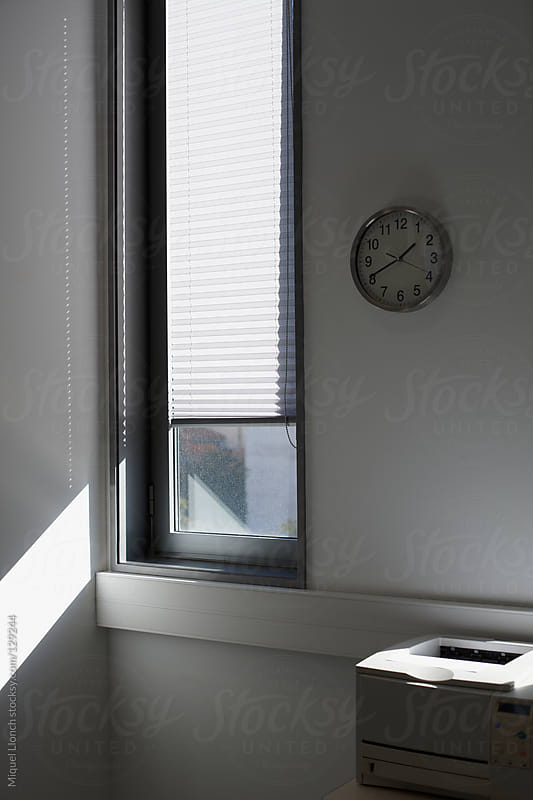 Wall clock and printer in a business office with a sunny window and nobody by Miquel Llonch for Stocksy United
