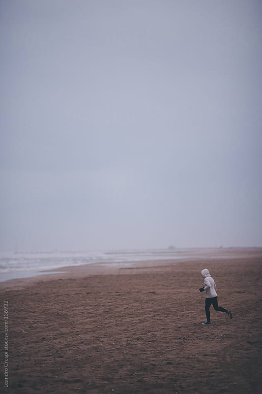 Man jogging on the beach by Leandro Crespi for Stocksy United
