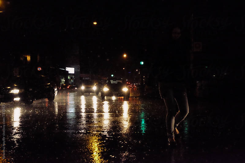 Anonymous person walking along a rainy street at night by Rowena Naylor for Stocksy United