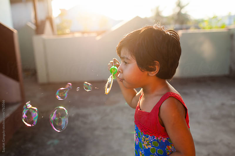 Little girl blowing bubbles at sunset by Saptak Ganguly for Stocksy United
