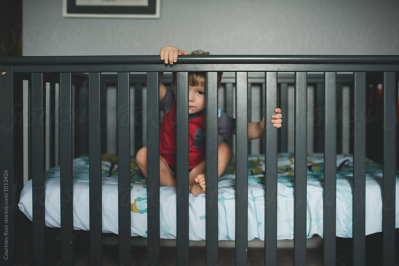 Toddler boy peeking through crib by Courtney Rust for Stocksy United