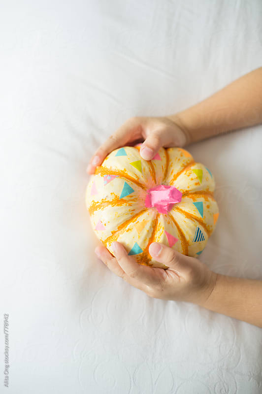Kid holding decorated pumpkin by Alita Ong for Stocksy United