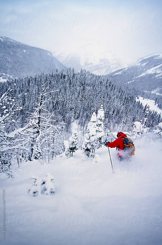 Man tree skiing powder snow in winter mountains of Rogers Pass,  by Soren Egeberg for Stocksy United